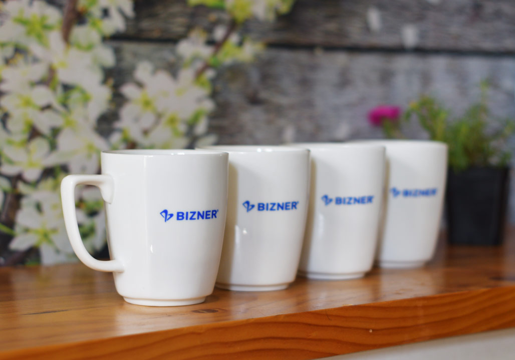 Ly sứ trắng vát góc in logo Bizner